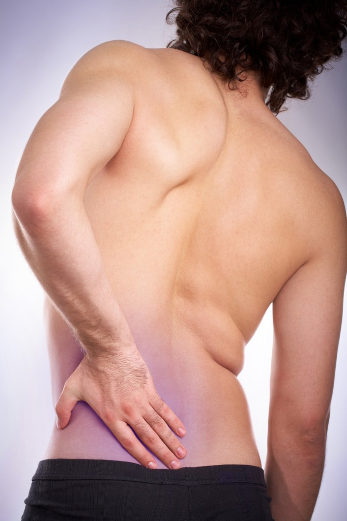 Back view of young man touching aching back